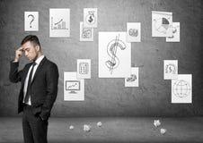 Hombre de negocios que especula con los carteles del negocio en el muro de cemento y trozos de papel en el piso fotografía de archivo libre de regalías