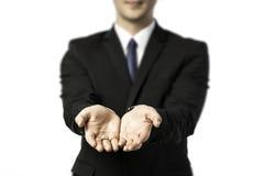 Hombre de negocios que estira hacia fuera ambas manos Imagenes de archivo