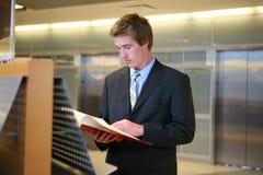 Hombre de negocios que estudia en biblioteca Fotografía de archivo libre de regalías