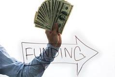 Hombre de negocios que exhibe una extensión del efectivo aislada en el fondo blanco Foto de archivo libre de regalías
