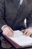 Hombre de negocios que firma un documento Imágenes de archivo libres de regalías