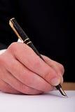 Hombre de negocios que firma un documento con la pluma Fotos de archivo libres de regalías
