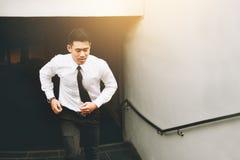 Hombre de negocios que funciona con para arriba la escalera que va a trabajar Imagen de archivo