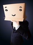 Hombre de negocios que gesticula con una caja de cartón en su cabeza con el smil Fotografía de archivo libre de regalías