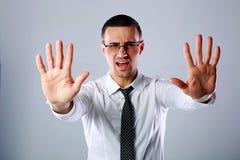 Hombre de negocios que gesticula la muestra de la parada con ambas manos Fotografía de archivo libre de regalías