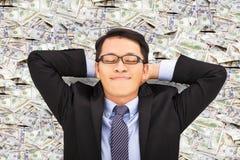 Hombre de negocios que goza y que miente en el dinero Imagenes de archivo