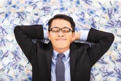 Hombre de negocios que goza y que miente en las pilas de dinero Imagenes de archivo