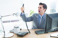 Hombre de negocios que grita como él celebra hacia fuera el teléfono en la oficina Imágenes de archivo libres de regalías