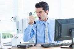 Hombre de negocios que grita como él celebra hacia fuera el teléfono en la oficina Imagen de archivo libre de regalías