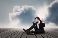 Hombre de negocios que grita debajo de las nubes Foto de archivo