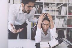 Hombre de negocios que grita en el colega femenino en oficina imagen de archivo