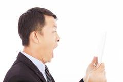 Hombre de negocios que grita en ipad o la tableta sobre blanco Foto de archivo