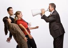 Hombre de negocios que grita en los compañeros de trabajo con el megáfono Fotos de archivo libres de regalías