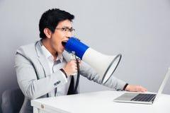 Hombre de negocios que grita en megáfono en el ordenador portátil Fotografía de archivo libre de regalías