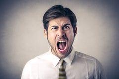 Hombre de negocios que grita hacia fuera ruidosamente Foto de archivo libre de regalías
