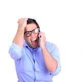 Hombre de negocios que grita mientras que teniendo conversación sobre el teléfono celular imagen de archivo libre de regalías