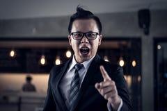 Hombre de negocios que grita y que señala el finger en usted porque él está muy enojado de los informes financieros disminuidos Fotografía de archivo libre de regalías