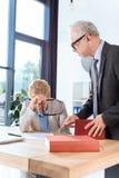 Hombre de negocios que habla con el colega con exceso de trabajo Fotos de archivo libres de regalías