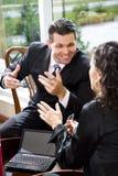 Hombre de negocios que habla con el compañero de trabajo hispánico femenino Fotos de archivo