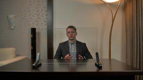 Hombre de negocios que habla con la cámara, mirando la exhibición transparente de cristal almacen de video