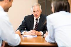 Hombre de negocios que habla con un par Imágenes de archivo libres de regalías
