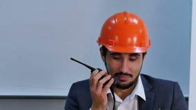Hombre de negocios que habla en el sistema de radio mientras que teniendo una reuni?n en oficina almacen de video
