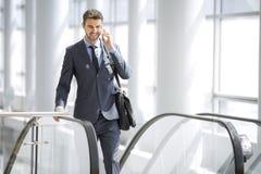 Hombre de negocios que habla en el teléfono celular mientras que en la escalera móvil fotografía de archivo libre de regalías