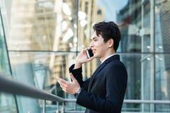 Hombre de negocios que habla en el teléfono con el fondo del edificio de la ciudad foto de archivo libre de regalías
