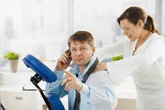 Hombre de negocios que habla en el teléfono durante masaje imagen de archivo libre de regalías