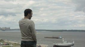 Hombre de negocios que habla en el teléfono elegante cerca del río almacen de metraje de vídeo