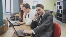 Hombre de negocios que habla en el teléfono en la oficina almacen de video