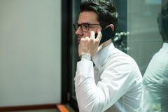 Hombre de negocios que habla en el teléfono en oficina Fotografía de archivo