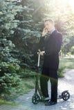 Hombre de negocios que habla en el teléfono en la vespa Foto de archivo