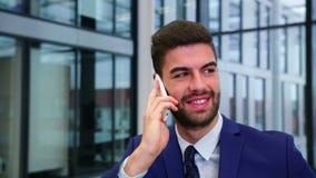 Hombre de negocios que habla en el teléfono móvil almacen de metraje de vídeo