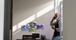 Hombre de negocios que habla en el teléfono móvil cerca de la ventana 4k almacen de video