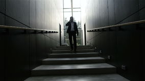 Hombre de negocios que habla en el teléfono móvil en pasillo de la oficina almacen de video