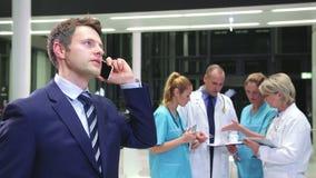 Hombre de negocios que habla en el teléfono móvil en pasillo del hospital metrajes