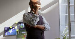 Hombre de negocios que habla en el teléfono móvil en la oficina 4k metrajes