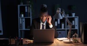 Hombre de negocios que habla en el teléfono móvil y que usa el ordenador portátil en la noche