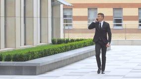 Hombre de negocios que habla en el teléfono mientras que camina a lo largo del edificio moderno almacen de metraje de vídeo