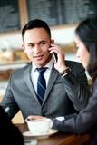 Hombre de negocios que habla en el teléfono mientras que hace frente con a sociedad Foto de archivo