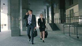 Hombre de negocios que habla en el teléfono y la mujer de negocios que caminan con él que tira de su maleta almacen de metraje de vídeo