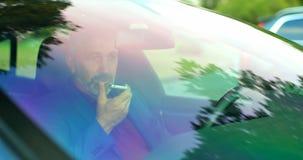 Hombre de negocios que habla en el tel?fono m?vil en un coche 4k almacen de metraje de vídeo