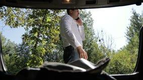 Hombre de negocios que habla en smartphone cerca del coche almacen de video