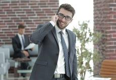 Hombre de negocios que habla en smartphone en su oficina Imagenes de archivo