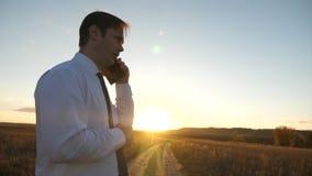 Hombre de negocios que habla en un smartphone contra el cielo hombre en un lazo con una tableta en el parque en la puesta del sol almacen de metraje de vídeo