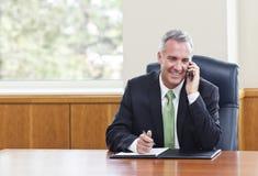 Hombre de negocios que habla en un teléfono celular fotografía de archivo libre de regalías