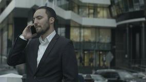 Hombre de negocios que habla por la situación elegante del teléfono almacen de metraje de vídeo