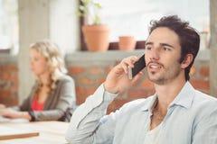 Hombre de negocios que habla sobre el teléfono en oficina Fotos de archivo