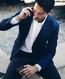 Hombre de negocios que habla vía smartphone moderno mientras que toma resto durante día del trabajo Sosteniéndose las manos se ll imagen de archivo libre de regalías